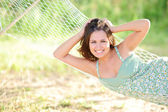 Woman lying on hammock in the park — Stock Photo