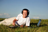 Smiling disc jockey on green grass — Stock Photo