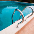 Swimming pool with stair and green relaxing water — Stock Photo