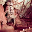 Cave stalactites and formations and a caver - Foto de Stock