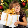 Pretty girl with present near the Cristmas tree — Stock Photo #7676377