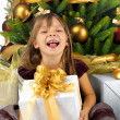 Stock Photo: Pretty girl with present near the Cristmas tree