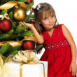 Pretty girl with present near the Christmas tree — Stock Photo #7676408