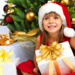 Pretty girl with present near the Cristmas tree — Stock Photo #7676418