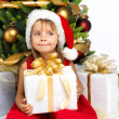 Pretty girl with present near the Cristmas tree — Stock Photo #7676421