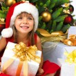 Pretty girl with present near the Christmas tree — Stock Photo #7676429