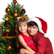 Mother and daughter near the Christmas tree — Stock Photo