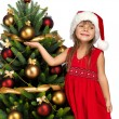 Pretty girl near the Cristmas tree - Stock Photo