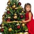 Pretty girl with present near the Christmas tree - Foto Stock
