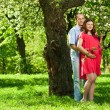 Pregnant woman in park with her husband - Stock fotografie