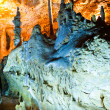 Cave stalactites and formations and a caver - Stock Photo