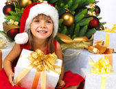 Pretty girl with present near the Christmas tree — Stok fotoğraf