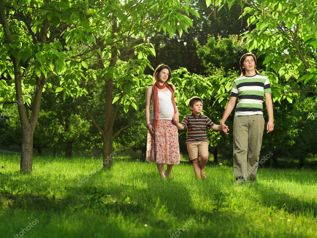 Happy Family walking outdoors. Husband, pregnant wife and their son — Stock Photo #7676182