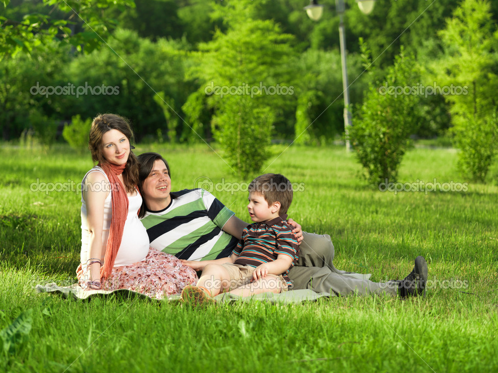 Happy Family walking outdoors. Husband, pregnant wife and their son — Stock Photo #7676192