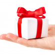 Gift box with red ribbon in hand — Stock Photo