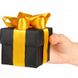 Black gift box with gold ribbon in hand — Stockfoto #7822594