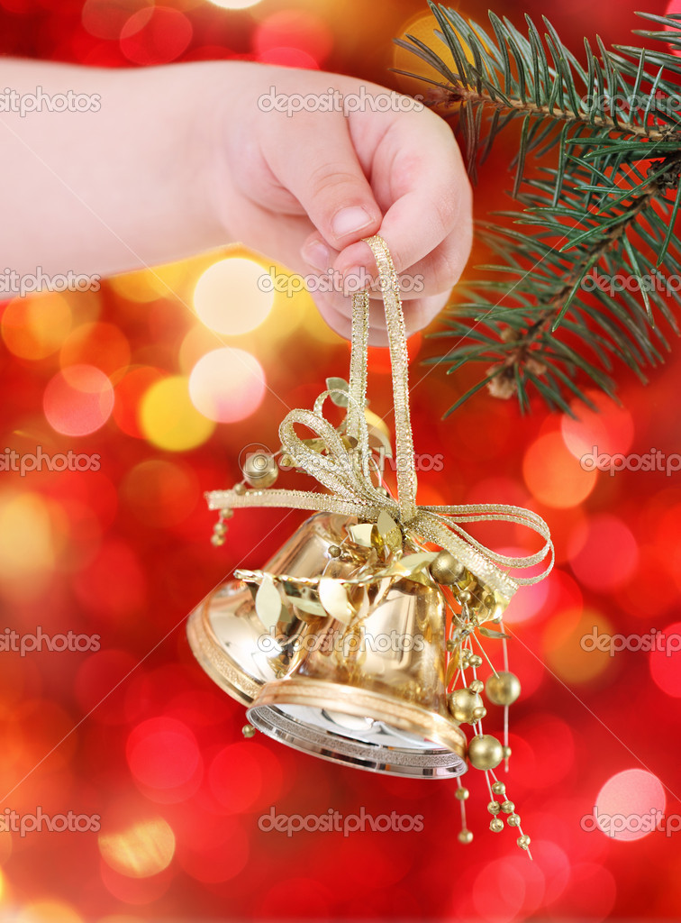 Child holding golden Christmas tree decorations on lights background — Stock Photo #6823557