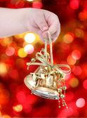 Child holding golden Christmas tree decorations — Stock Photo