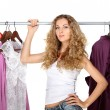 Portrait of a blonde beautiful girl selecting clothes - Photo