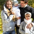 Young happy family in autumn forest — Stock Photo #7614363