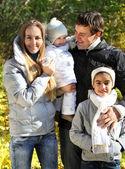 Junge glückliche familie im herbst wald — Stockfoto