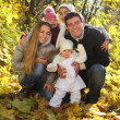 Young happy family in autumn forest — Stock Photo