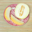 Ripe half melon and slices on antique plate — Foto de Stock