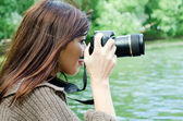 The young girl with the camera in park — Stock Photo