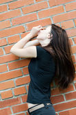 Young sad girl at brick walls — Stock Photo