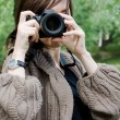 The young girl with the camera in park - Stock Photo