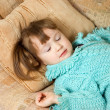 Little girl sleeps on a sofa - Stok fotoğraf