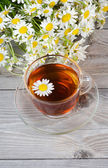 Glass cup with a camomile tea — Stock Photo