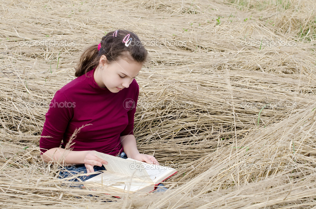 The girl reads the book on grass — Stock Photo #7545628