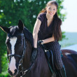 Young girl riding black sport horse — Stock Photo
