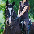 Stock Photo: Young girl riding black sport horse