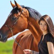 Young girl and bay horse — Stock Photo #7910459