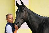 Dziewczyna i czarny koń sportowy przed konkursy — Zdjęcie stockowe