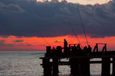 Fishermans on a pier in the evening on a sea — Stock Photo
