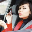 Pretty caucasian woman in a car doing makeup. — Stock Photo