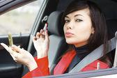 Pretty caucasian woman in a car doing makeup. — Stock Photo