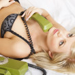 Pensive woman with the green telephone — Stock Photo