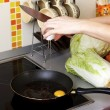 Woman cracking eggs into frying pan in kitchen — Stock Photo