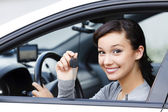 Pretty asian female driver in a white car showing the car key — Stock Photo