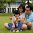 Happy family sits on grass field — Stock Photo