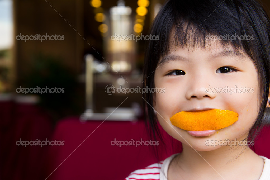 Adorable little girl eating a slice of orange with smiling face — Stock Photo #7595908