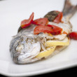 Sea bream with tomatoes and lemon — Stock Photo
