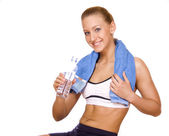 Young woman with bottle in the hand after fitness. Isolated over white — Stock Photo