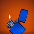 Blue zippo lighter with flame on orange background — Stock Photo #7368873