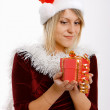 Girl in santa hat with a gift — 图库照片