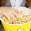Royalty-Free Stock Photo: Hand in a bucket of popcorn